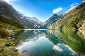 foto of snow capped mountains  - Peaks of Darran Mountains reflecting in a Lake Marian - JPG