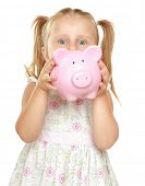 The little girl with a money box - a pig. It is isolated on a white background