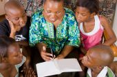 image of girl reading book  - A happy african mother reading a book to her 4 children in living room - JPG