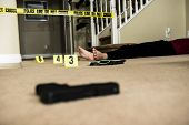 pic of crime scene  - a body on the ground of a crime scene with a gun in the foreground - JPG