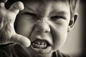 picture of irritated  - Black and white photo of a boy in an angry grimassy closeup - JPG