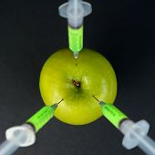 picture of modification  - Red modification liquid in the syringe injected into green apple top view - JPG