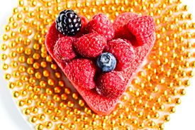stock photo of hackney  - Heart shaped cake with berries on top and with a gold beads - JPG