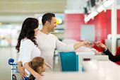 stock photo of over counter  - cheerful family handing over air ticket at airport at check in counter - JPG
