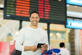 image of boarding pass  - happy middle aged man holding passport and boarding pass in front of flight information board at airport - JPG