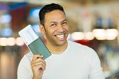 image of boarding pass  - cheerful mid age man holding passport and boarding pass at airport - JPG