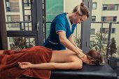 stock photo of therapist massage  - A massage therapist is treating a female client on a table in an apartment - JPG