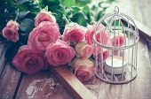 foto of caged  - Bouquet of pink roses wooden frame and a burning candle in a white decorative bird cage on old board background vintage decor and color tinting - JPG
