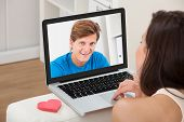 pic of long distance relationship  - Cropped image of young woman video chatting with boyfriend on laptop at home - JPG