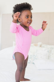 stock photo of babygro  - Baby girl in pink babygro standing on bed at home in the bedroom - JPG