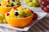 stock photo of hollow  - Fruit salad with grapes currants pears kiwi in hollowed - JPG