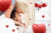 picture of fiance  - Woman kissing her fiance on the forehead against love heart pattern - JPG