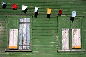 stock photo of choke  - Green wall of an old house with a window and choked flags - JPG