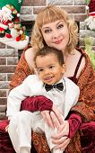 image of new years baby  - Happy mother and black baby boy cuddling by fireplace - JPG
