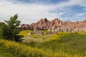 stock photo of rock carving  - Dramatic mountain formations carved out by erosion showing layers of rocks with spring wildflowers - JPG