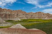 pic of rock carving  - Dramatic mountain formations carved out by erosion showing layers of rocks with spring wildflowers - JPG