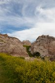 pic of rock carving  - Dramatic mountain formations carved out by erosion showing layers of rocks with spring wildflowers below in Badlands National Park South Dakota - JPG