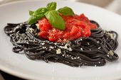 foto of cuttlefish  - Cuttlefish ink spaghetti with Parmesan cheese and tomato sauce decorated with basil leaf - JPG