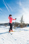 picture of nordic skiing  - Woman cross country skiing on a yellow skis - JPG