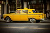 stock photo of cabs  - A great old historic Yellow Cab on an urban city street - JPG