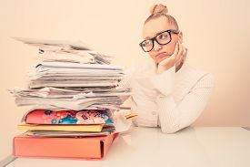 stock photo of adversity humor  - Inquiet business woman looking at her stack of documents  - JPG