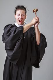 pic of toga  - Woman in her thirties wearing a canadian lawyer toga screaming with a gavel in the air - JPG