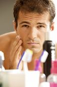 foto of shaved head  - Reflection of young man in mirror applying shaving cream - JPG