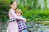 stock photo of little sister  - Outdoor portrait of two adorable kids - JPG
