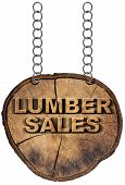 pic of lumber  - Wooden sign a section of tree trunk with text lumber sales hanging with metal chain - JPG