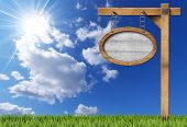 stock photo of oval  - Empty oval wooden sign with wooden brown frame hanging with metal chain on a wooden pole on blue sky with clouds sun rays and green grass - JPG