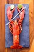 pic of lobster tail  - Close up Red Lobster Clipping Lime Slices on a Gray Cutting Board with Picks Served on Top of a Wooden Table - JPG