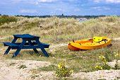 stock photo of kayak  - Orange and yellow kayak on a sandy dune by the sea - JPG