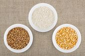 stock photo of buckwheat  - Small glass bowls with dry rice buckwheat and peas shelled on burlap - JPG
