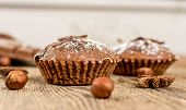 image of chocolate muffin  - Cocoa and chocolate muffin with hazelnut nad sugar on wood table - JPG