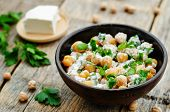 stock photo of chickpea  - salad with chickpeas feta and parsley on a dark wood background - JPG