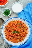 stock photo of millet  - millet porridge with tomato sauce garlic and parsley on a white wood background - JPG