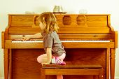 stock photo of stool  - Right note requires effort outside your comfort zone in a conceptual image with a little girl climbing on the stool to stretch across a piano keyboard for the correct key or note - JPG