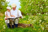 image of grandfather  - grandfather reading a book to his grandson in blooming garden - JPG