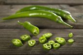 picture of chillies  - Chopped Fresh green chilli pepper On A rustic Wooden Board - JPG