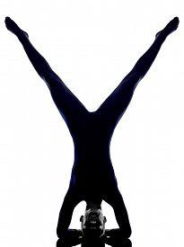 stock photo of scorpion  - woman exercising vrschikasana scorpion pose yoga silhouette shadow white background - JPG
