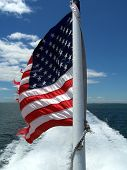 stock photo of usa flag  - American fag flying off the back of a ship - JPG