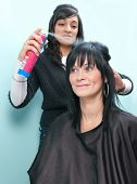 foto of hairspray  - Beautiful young woman receives hairspray from attractive Indian hair stylist - JPG