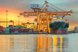 stock photo of shipyard  - Industrial Container Cargo freight ship with working crane bridge in shipyard at dusk for Logistic Import Export background - JPG