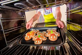 stock photo of gingerbread man  - Baking Gingerbread man in the oven - JPG