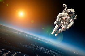 stock photo of outer  - Astronaut in outer space against the backdrop of the planet earth - JPG