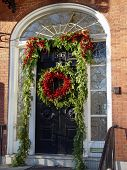 stock photo of christmas wreath  - a beautiful red and green xmas wreath hangs in the middle of a door surrounded by pine garland and more holly berries