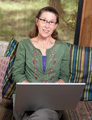 stock photo of screen-porch  - Pretty middle age mature woman looking directly at camera while working at her laptop computer - JPG
