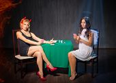Постер, плакат: Angel and devil playing cards at room