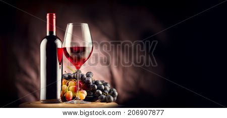 poster of Wine. Bottle and glass of Red wine with ripe grapes still life. Red wine Over black background. Bord