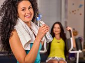 Woman in gym workout with fitness equipment. Girl drink from bottle water relaxing after workout at  poster